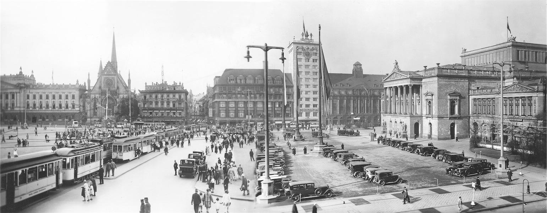 """Der Leipziger Augustusplatz mit dem Neuen Theater, um 1930     Das Leipziger """"Neue Theater"""" wurde in den Jahren 1864 bis 1868 von Carl Ferdinand Langhans an der Nordseite des Augustusplatzes erbaut. Es besaß 1700 Sitz- und 300 Stehplätze. Errichtet wurde das Haus als Nachfolgerbau für das """"Alte Theater"""" am Fleischerplatz (heute Richard-Wagner-Platz), das als Spielstätte dem Leipziger Schauspiel zugesprochen wurde.     Von 1935 bis 1938 wurden Bühne und Orchestergraben des Neuen Theaters vergrößert, um den gewachsenen Anforderungen des neueren Opernschaffens zu entsprechen. In der Nacht vom 3. zum 4. Dezember 1943 zerstörten englische Fliegerbomben neben dem Alten Theater und dem Neuen Gewandhaus auch den Zuschauerraum und die Bühne des Neuen Theaters. An jenem Abend hatte sich der Vorhang noch für Wagners """"Walküre"""" geöffnet und das Publikum dem """"Feuerzauber"""" (!) gelauscht ... Am Dirigentenpult vor dem Gewandhausorchester hatte Paul Schmitz gestanden.     Die Ruine des ausgebrannten Opernhauses wurde – obwohl deutlich weniger zerstört als die Dresdener Semperoper – 1950 abgetragen, um dem 1960 eingeweihten ersten Opernneubau der DDR Platz zu machen."""