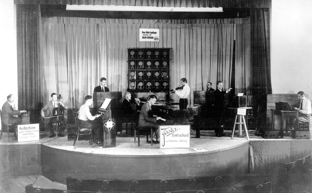 """""""Elektrische Konzerte"""" mit dem elektroakustischen Orchester, 1932/1933  Anlässlich der 9. und 10. Funkausstellung in Berlin 1932 und 1933 fanden erstmals Konzerte mit """"Elektrischer Musik"""" statt. Gespielt wurden vom sogenannten """"Orchester der Zukunft"""" alle damals verfügbaren elektroakustischen Musikinstrumente. Diese erzielten seinerzeit ein außerordentlich großes Interesse und auch breite Zustimmung in der Öffentlichkeit, wie der mit eigenem Theremingerät mitwirkende Erich Zitzmann-Zerini [zweiter von rechts] dem Toningenieur Gerhard Steinke erzählte und ihm dabei dieses Originalfoto übergab.Die Orchesterbesetzung bestand aus zwei Theremin-Instrumenten, Trautonium (nach Trautwein), Hellertion (von B. Helberger und P. Lertes), einem Neo-Bechstein-Flügel (nach Vorschlä-gen von O. Vierling, S. Francó, W. Nernst und H. Driescher), Vierling-Klavier (Elektroakusti-sches Klavier von O. Vierling), Elektro-Geige, Elektro-Cello und Saraga-Generator (ein licht-elektrisches Gerät von W. Saraga, prinzipiell ähnlich dem Theremingerät."""